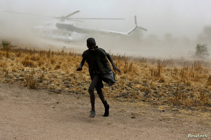 A boy moves away as a United Nations World Food Program helicopter lands in Rubkuai village, Unity State, northern South Sudan, Feb. 18, 2017.