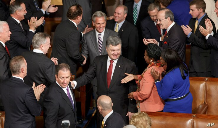 Ukrainian President Petro Poroshenko, escorted by House Majority Leader Kevin McCarthy, R-Calif., is welcomed by U.S. lawmakers as he arrives to address a joint session of Congress, at the Capitol in Washington, Thursday, Sept. 18, 2014. Poroshenko i...