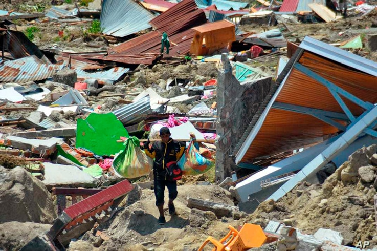 A man carry items he saved from the rubble following a major earthquake and tsunami in Palu, Central Sulawesi, Indonesia, Monday, Oct. 1, 2018.