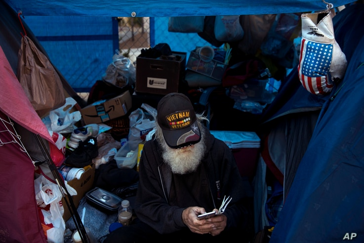 """Theodore Neubauer, a 78-year-old Vietnam War veteran, who is homeless, looks at his smartphone while passing time in his tent, Dec. 1, 2017, in Los Angeles. """"Well, there's a million-dollar view,"""" said Neubauer on what it's like to be homeless in Los ..."""