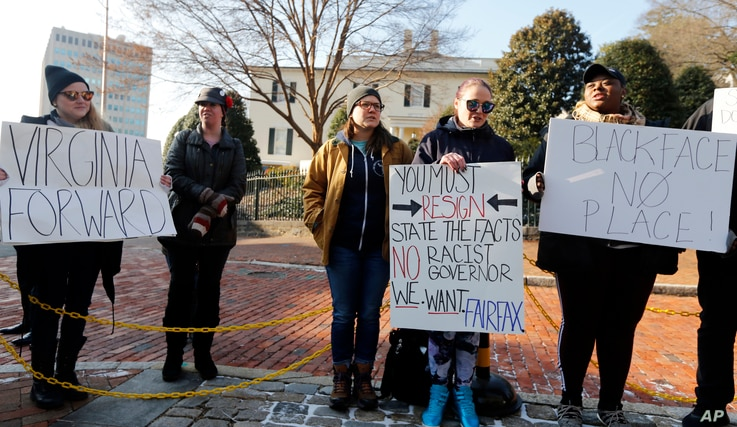 Demonstrators hold signs and chant outside the Governor's Mansion at the Capitol in Richmond, Va., Feb. 2, 2019. The demonstrators were calling for the resignation of Virginia Gov Ralph Northam after a decades-old, racially insensitive photo from his...