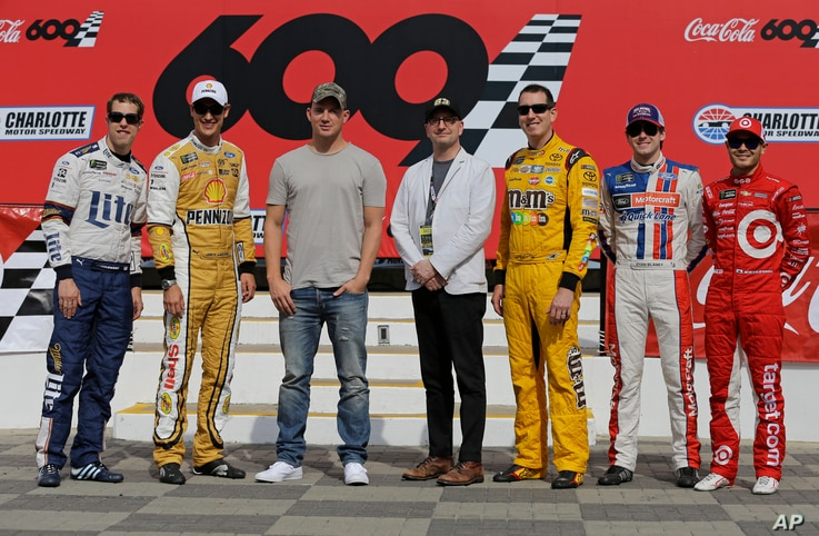 FILE - Actor Channing Tatum, third from left, and director Steven Soderbergh, center, pose for a photo with NASCAR drivers, from left to right, Brad Keselowski, Joey Logano, Kyle Busch, Ryan Blaney and Kyle Larson before the NASCAR Cup series auto ra...