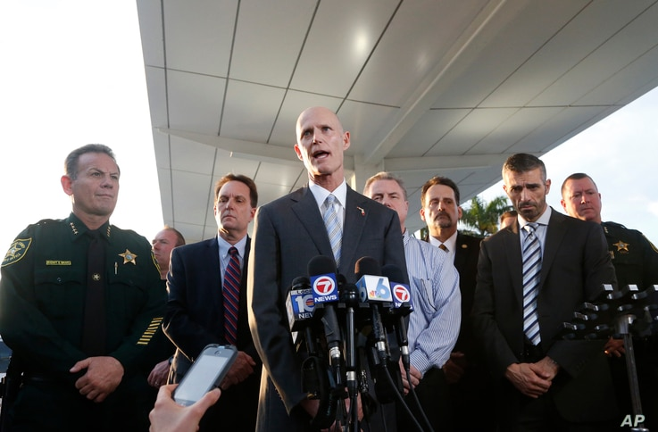 Joined by law enforcement officials, Florida Gov. Rick Scott (center) speaks during a news conference outside Fort Lauderdale–Hollywood International Airport, Jan. 6, 2017, in Fort Lauderdale, Fla.