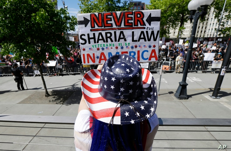 Cathy Camper, of Tacoma, Wash., wears a stars-and-stripes cowboy hat as she protests against Islamic law at a rally, June 10, 2017, in Seattle, as counter-protesters demonstrate across the street.