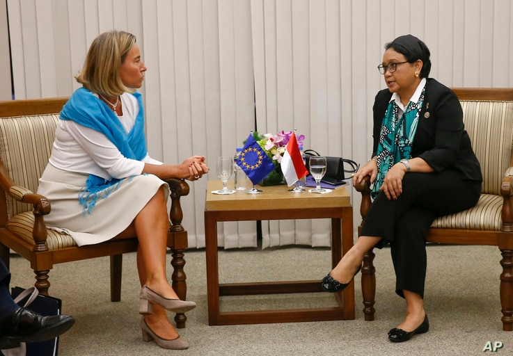 European Union Foreign Policy Chief Federica Mogherini, left, and Indonesian Foreign Minister Retno Marsudi talk during a meeting on the sidelines of the 50th ASEAN Foreign Ministers' Meeting and Related Meetings in Manila, Philippines, Monday, Aug. ...