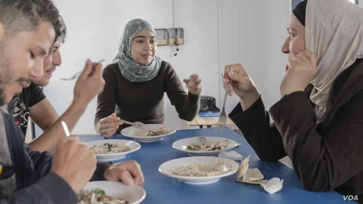A group of refugees enjoys one of the daily lunches served at the Khora center, in the Exarchia district in Athens, Greece, Oct. 24, 2016.
