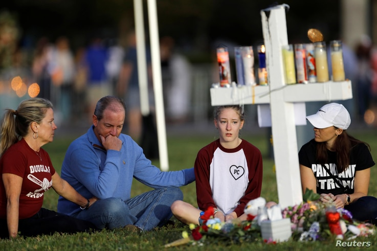 A family sits around one of 17 crosses at a memorial for the victims of the shooting at Marjory Stoneman Douglas High School in Parkland, Florida, Feb. 16, 2018.