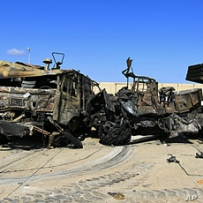 Destroyed military vehicles are seen at a naval military facility after last night's coalition air strikes in People's Port in eastern Tripoli, March 22, 2011