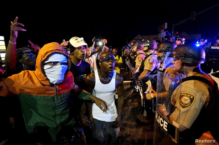 Protesters yell at a police line shortly before shots were fired in a police-officer involved shooting in Ferguson, Missouri August 9, 2015