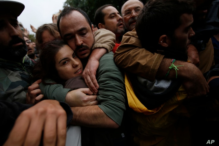 Pro-referendum supporters embrace each other as Spanish National Police tries to remove them from the Ramon Llull school assigned to be a polling station by the Catalan government in Barcelona, Spain, early Oct. 1 2017.