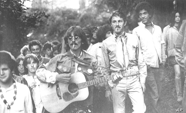 FILE - George Harrison, a member of the British pop group, the Beatles, pays a surprise visit to San Francisco's famed Haight-Ashbury hippy district, Aug. 8, 1967.