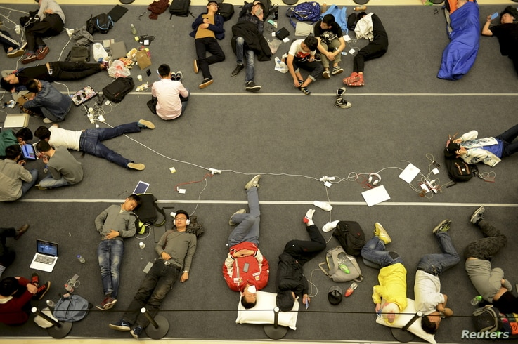 People sleep on the floor as they line up for the opening of a new Apple Store in Hangzhou, Zhejiang province, China, April 24, 2015.