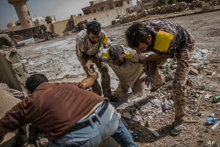 A fighter of the Libyan forces affiliated to the Tripoli government is helped by comrades after being shot by a sniper, in Sirte, Libya, Oct. 2, 2016.