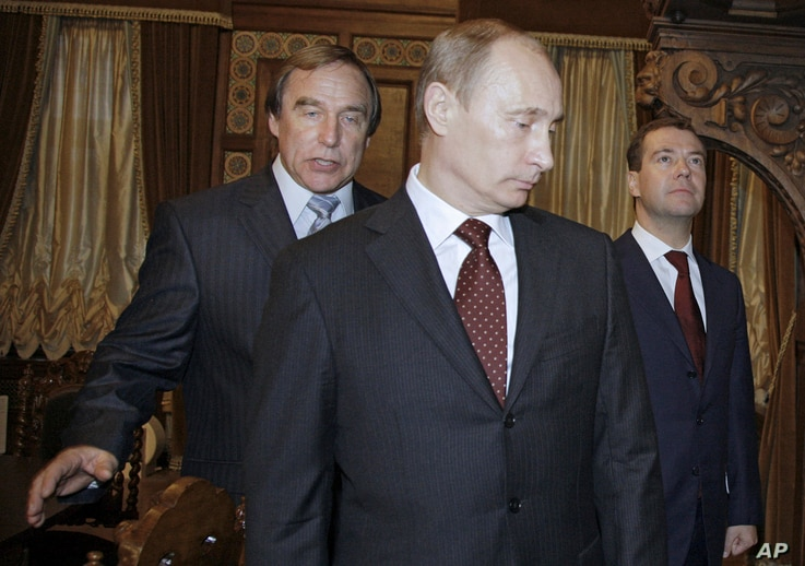 FILE - In this Nov.  21, 2009 file photo, Russian cellist and House of Music Director Sergei Roldugin, left, escorts then Russian Prime Minister Vladimir Putin, center, and President Dmitry Medvedev as they tour a restored House of Music, a former pa...