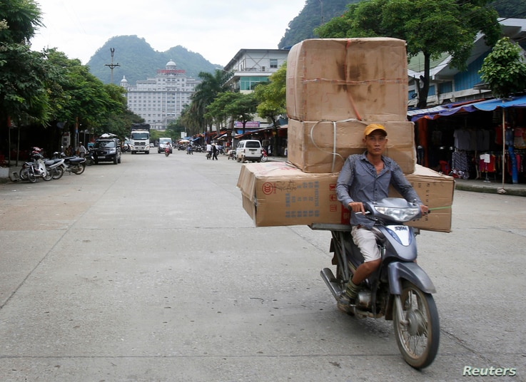 A man transports boxes of Chinese goods at Tan Thanh market, on the border with China, in Vietnam's northern Lang Son province July 30, 2014.