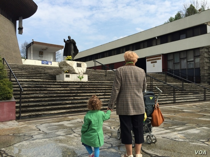 A grandmother and granddaughter look up at a statue of Pope John Paul II at the Ark of the Lord church, Cracow, Poland, April 23, 2014. (Jerome Socolovsky/VOA)