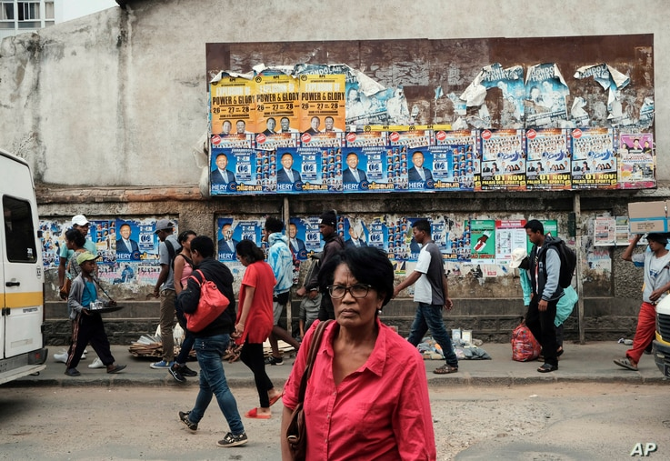 Pedestrians pass a wall with election posters in Antananarivo, Madagascar, Nov. 6, 2018 on the eve of elections in the Indian Island nation.