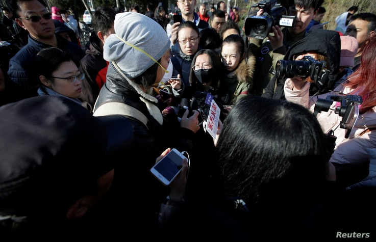 A parent is surrounded by members of the media outside the kindergarten run by preschool operator RYB Education Inc being investigated by China's police, in Beijing, China, Nov. 24, 2017.