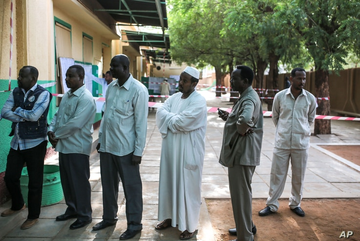 Voters queue outside a polling station on the first day of Sudan's presidential and legislative elections, in Khartoum, Sudan, April 13, 2015.