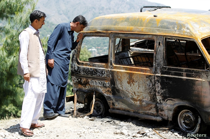 People look at the van in which Ambreen Riasat was burned in the village of Makol outside Abbottabad, Pakistan, May 6, 2016.
