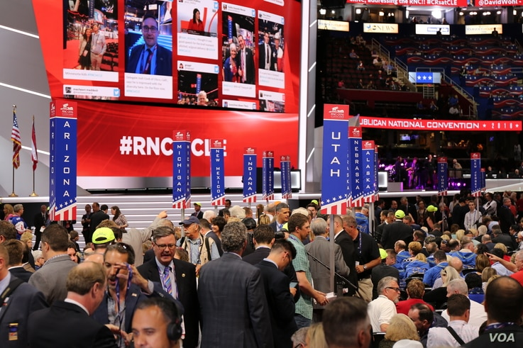 Delegates mingle before the start of Monday night's program on the floor of the Republican National Convention being held at Quicken Loans Arena in Cleveland, July 18, 2016.