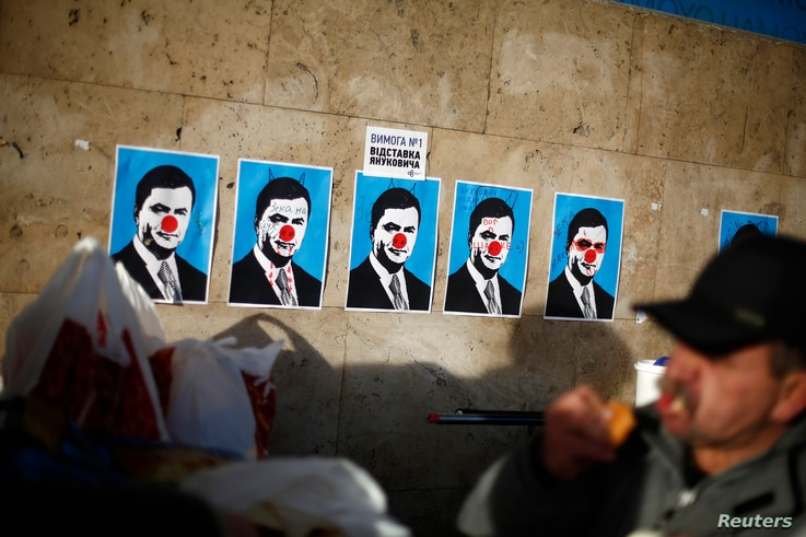 A man eats next to defaced posters depicting Ukranian President Viktor Yanukovich at Independence Square in Kiev December 4, 2013. Ukraine's prime minister warned protesters blockading government buildings on Wednesday that anybody guilty of violatin