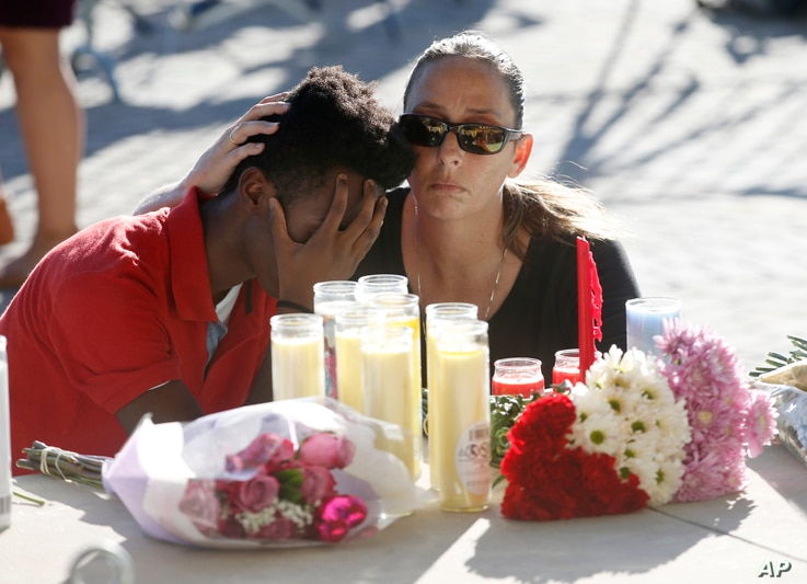 Pamela Tilton, right, comforts Che James-Riley, 18, as they light a candle at a memorial for the victims of the shooting at Marjory Stoneman Douglas High School, Feb. 15, 2018, in Parkland, Florida.