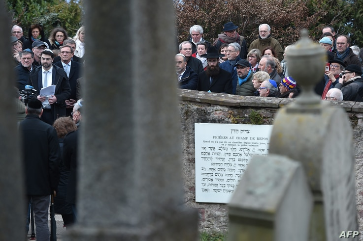 People take part in a remembrance ceremony during a rally in the Jewish cemetery of Quatzenheim, eastern France, on March 3, 2019.