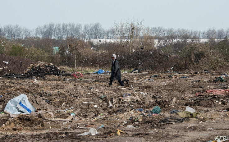 """A man walks among remains of taken down shelters during the dismantling of the southern part of the so-called """"Jungle"""" migrant camp in Calais, northern France, March 10, 2016."""