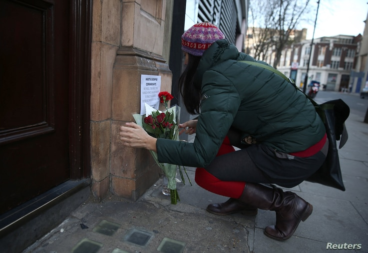 A woman places flowers as a tribute outside the Cuban Embassy in London, following the announcement of the death of Cuban revolutionary leader Fidel Castro, central London, Britain November 26, 2016.