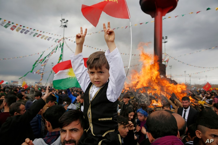 People are seen gathered around a bonfire after Turkish authorities permitted a Newroz celebration, in predominantly Kurdish Diyarbakir, Turkey, March 21, 2017.