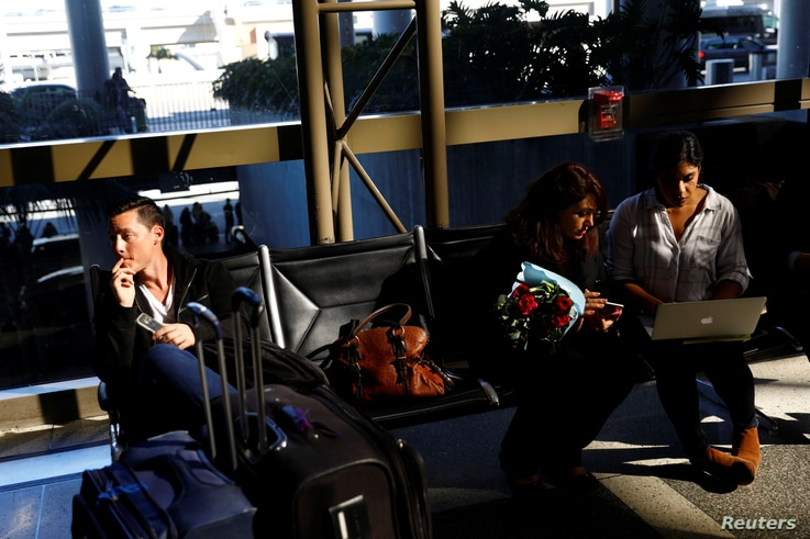 A passenger, left, waits in Los Angeles International Airport for his girlfriend, who was born in Iran but holds a Canadian passport and had not been allowed entry to the U.S. after vacationing in Thailand. Meanwhile, an attorney works to help family...