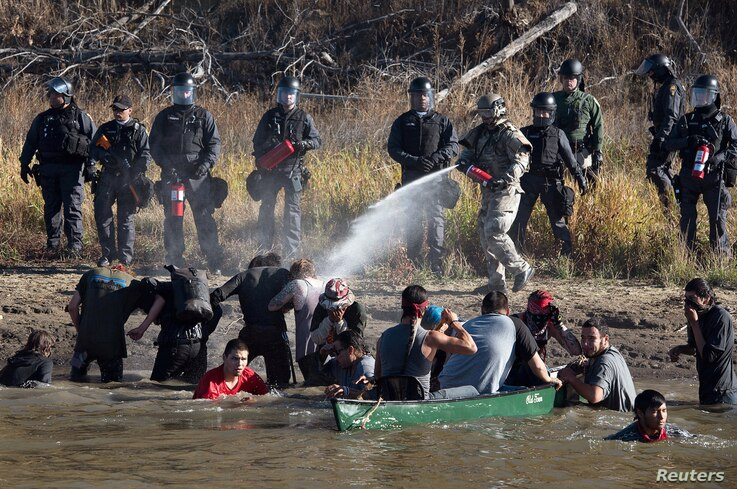 Police use pepper spray against protesters trying to cross a stream near an oil pipeline construction site near Standing Rock Indian Reservation, north of Cannon Ball, North Dakota, Nov. 2, 2016.