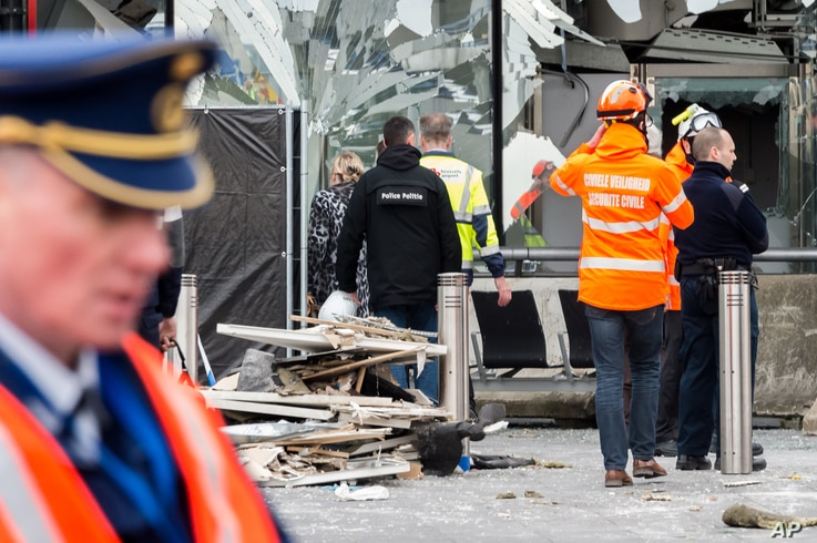 Police and other emergency workers stand in front of the damaged Zaventem Airport terminal in Brussels on March 23, 2016.