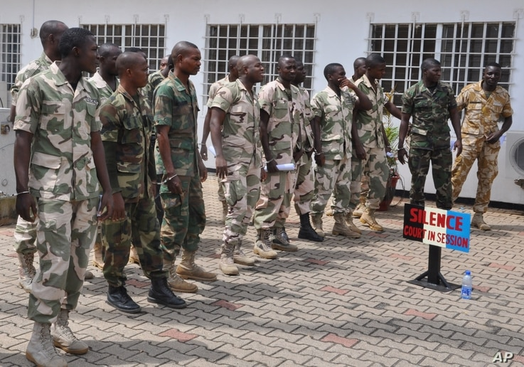 FILE - Soldiers accused of refusing to fight in the country's northeastern Islamic uprising appear before a court martial in Abuja, Nigeria, Oct. 2, 2014. The mass trial comes two weeks after 12 soldiers were sentenced to death by firing squad for mu...