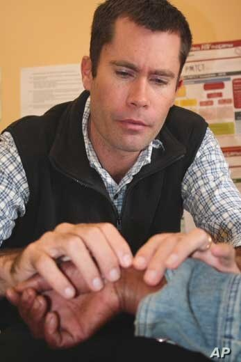 The hospital's chief physician, Ben Gaunt, carefully examines a patient