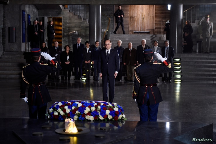 French President Francois Hollande (C) pays his respects after he placed a wreath at the Shoah memorial in Paris, Jan. 27, 2015.