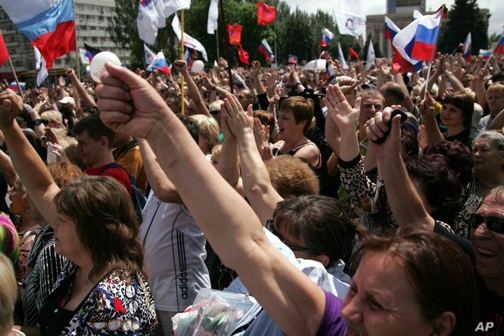 Demonstrators, holding Russian flags, rally for Russian protection and against war in Donetsk, eastern Ukraine, May 31, 2014.