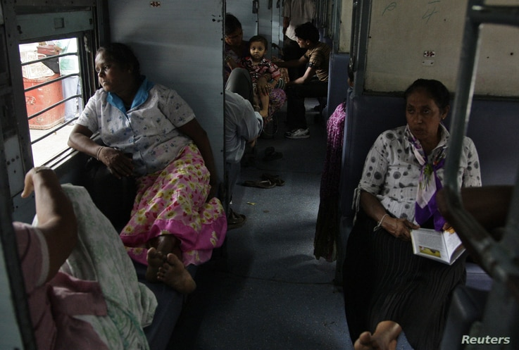 Passengers sit in a train as they wait for electricity to be restored at a railway station in the northern Indian city of Allahabad, July 30, 2012.