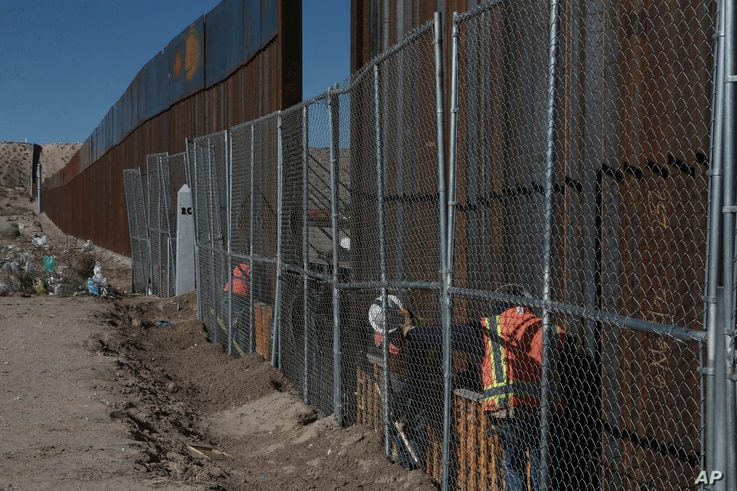 Workers continue work raising a taller fence in the Mexico-US border separating the towns of Anapra, Mexico and Sunland Park, New Mexico, Jan. 25, 2017.