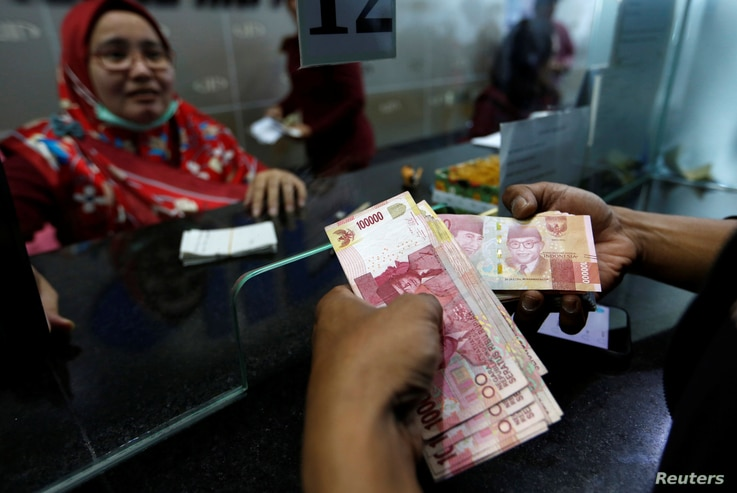 A customer holds Indonesian rupiah bank notes at a money changer in Jakarta, Indonesia, Aug. 13, 2018.