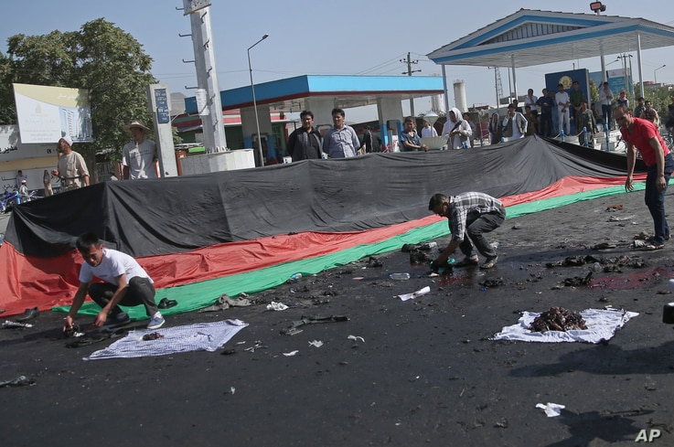 Afghans gather property, left behind by victims of a deadly explosion that struck a protest march by ethnic Hazaras, in Kabul, Afghanistan, Saturday, July 23, 2016.