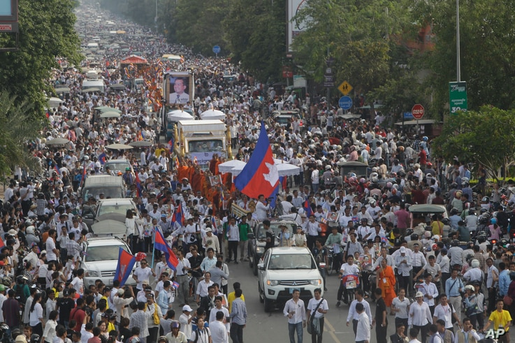 FILE - Cambodia mourners march during a funeral procession of Cambodia prominent political analyst Kem Ley in Phnom Penh, Cambodia, July 24, 2016. Tens of thousands of Cambodians marched in the procession for the leading government critic who was fat...