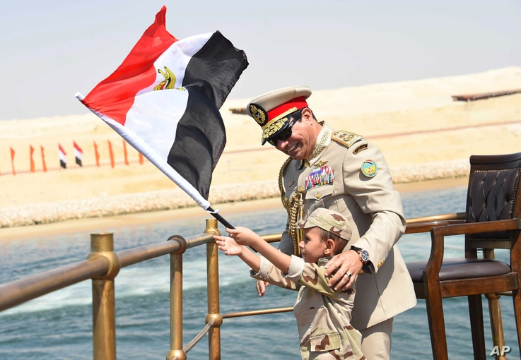 In this picture provided by the office of the Egyptian Presidency, President el-Sissi smiles at a boy dressed in a tiny military uniform as he waves the national flag from a monarchy-era yacht that sailed to the venue of a ceremony for extension of t...