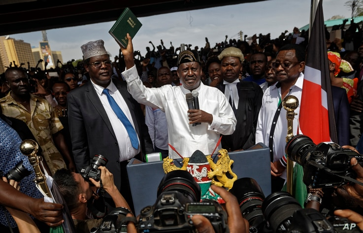"""Opposition leader Raila Odinga holds a bible aloft after swearing an oath during a mock """"swearing-in"""" ceremony at Uhuru Park in downtown Nairobi, Kenya, Jan. 30, 2018."""