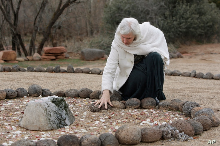 FILE - In this Jan. 27, 2010 photo, Angel Valley Retreat Center owner Amayra Hamilton pauses at a memorial marking the site where three people died during a sweat lodge ceremony in October 2009 in Sedona, Ariz.