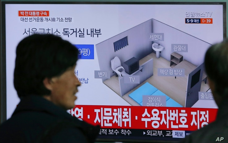 People watch a TV screen showing an image of solitary cell of Seoul Detention Center used by former South Korean President Park Geun-hye during a news program at the Seoul Railway Station in Seoul, South Korea, March 31, 2017.