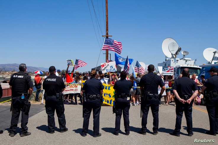 FILE - Demonstrators picket before the possible arrival of undocumented migrants who may be processed at the Murrieta Border Patrol Station in Murrieta, California, July 4, 2014.