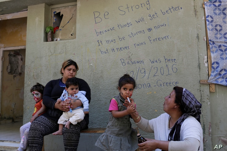 In this photo taken on Sept. 13, 2016, a Kurd Syrian mother gives cough syrup to her child at Ritsona refugee camp north of Athens.