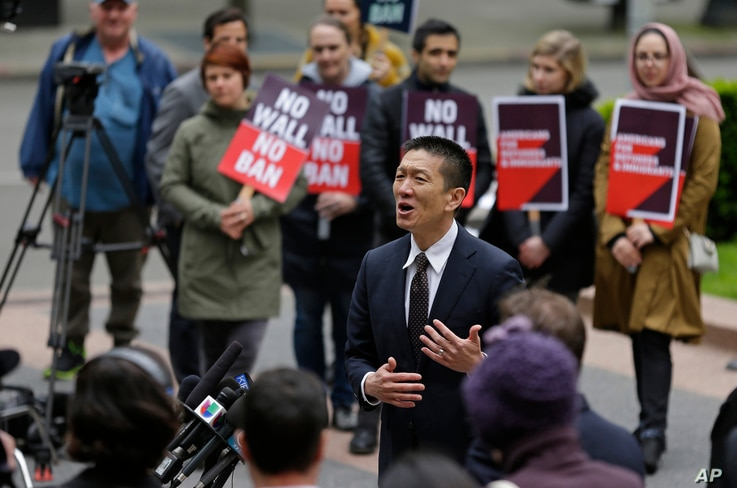 Hawaii Attorney General Doug Chin, center, talks to reporters outside a federal courthouse in Seattle, May 15, 2017.